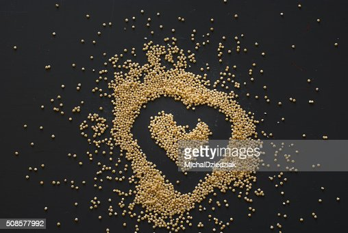 millet heart on dark wooden table : Stock Photo