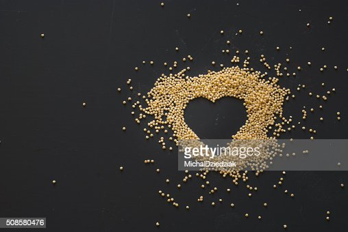 millet heart on dark wooden table : Stockfoto