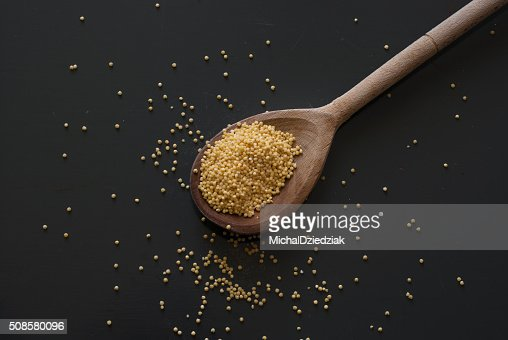 millet on wooden spoon on dark wooden table : Stock Photo