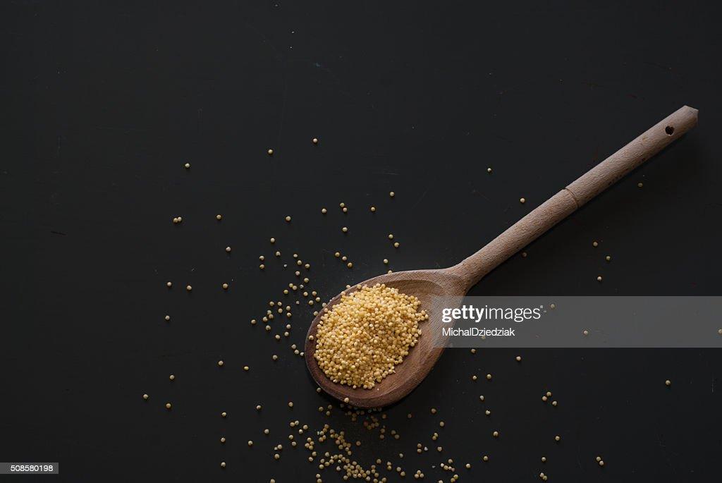 millet on wooden spoon on dark wooden table : Stock Photo