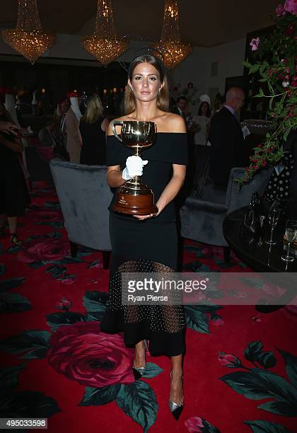 Millie Mackintosh poses with the Melbourne Cup at the Emirates Marquee on Derby Day at Flemington Racecourse on October 31 2015 in Melbourne Australia
