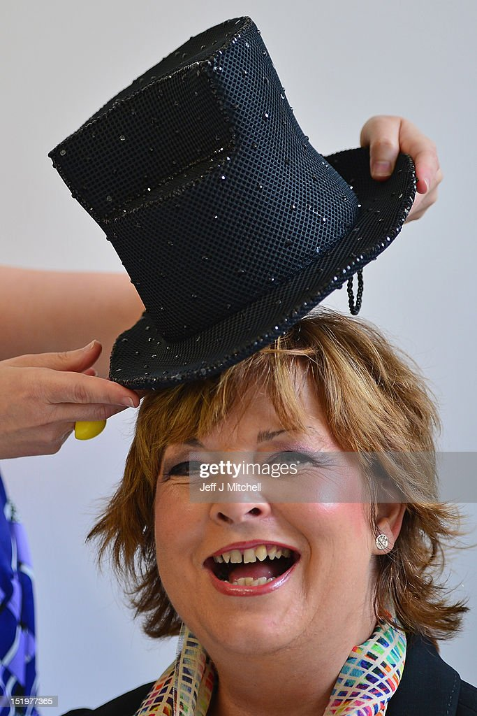 Milliner Pea Cooper places a hat on Fiona Hyslop, Cabinet Secretary for Culture and External Affairs, at the launch of Fashion Foundray on September 14, 2012 in Glasgow, Scotland. Fashion Foundry, a new initiative led by Cultural Enterprise Office in association with Wasps Studios, will see 10 of Scotland's most promising fashion designers helped in developing their businesses so as to target the lucrative luxury market both at home and overseas. It was launched by MSP Cabinet Secretary for Culture Fiona Hyslop.