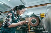 young beautiful milling machining worker using abrasive wheel tool grinding metal components .