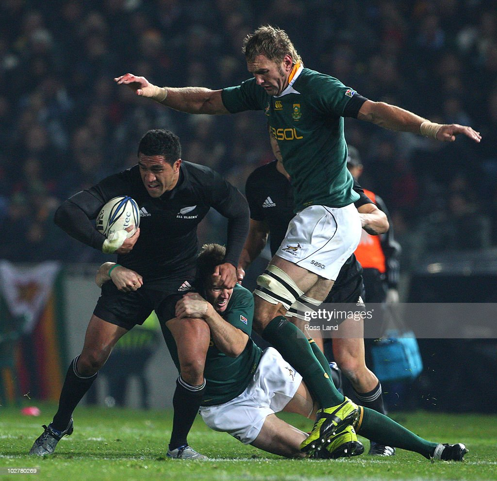 Mills Muliaina of the All Blacks is tackled by Francois Louw and Andries Bekker of the Springboks during the TriNations match between the New Zealand...