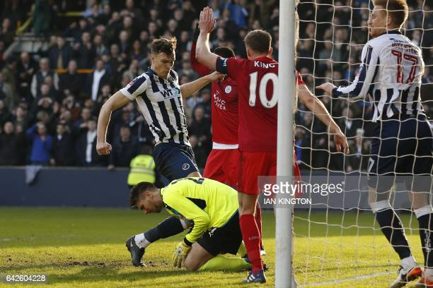 Millwall's English defender Jake Cooper is booked for this challenge on Leicester City's German goalkeeper RonRobert Zieler during the English FA Cup...