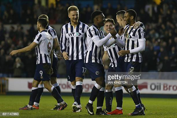 Millwall's Englishborn Jamaican defender Shaun Cummings celebrates with teammates after scoring their second goal during the English FA Cup third...