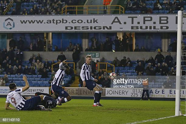 Millwall's Englishborn Jamaican defender Shaun Cummings scores their second goal during the English FA Cup third round football match between...