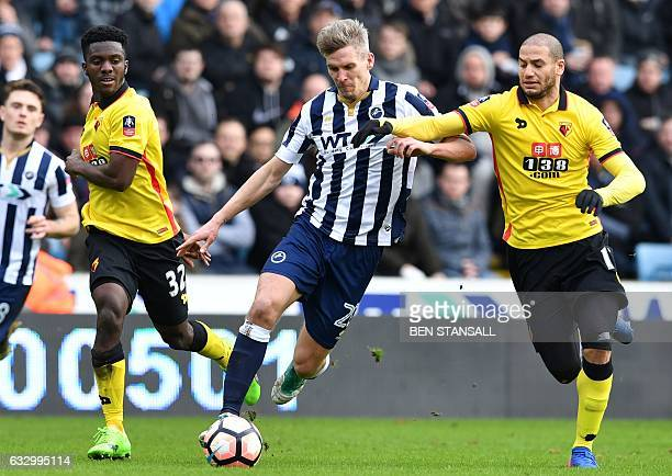 Millwall's Englishborn Welsh striker Steve Morison vies with Watford's French midfielder Adlene Guedioura during the English FA Cup fourth round...