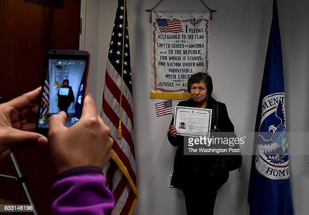 Milma Carlos poses with her citizenship certificate in front of a Pledge of Allegiance banner after the ceremony Thirtysix people from 22 countries...