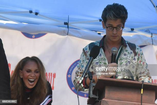 Milo Yiannopoulos speaks at an Alt Right protest of Muslim Activist Linda Sarsour as Pamela Geller laughs behind him on April 25 2017 in New York City