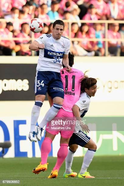 Milos Degenek and Jun Amano of Yokohama FMarinos compete against Yohei Toyoda of Sagan Tosu during the JLeague J1 match between Sagan Tosu and...