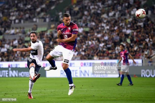 Milos Degenek of Yokohama FMarinos shoots while Lukas Podolski of Vissel Kobe tries to block it during the JLeague match between Vissel Kobe and...