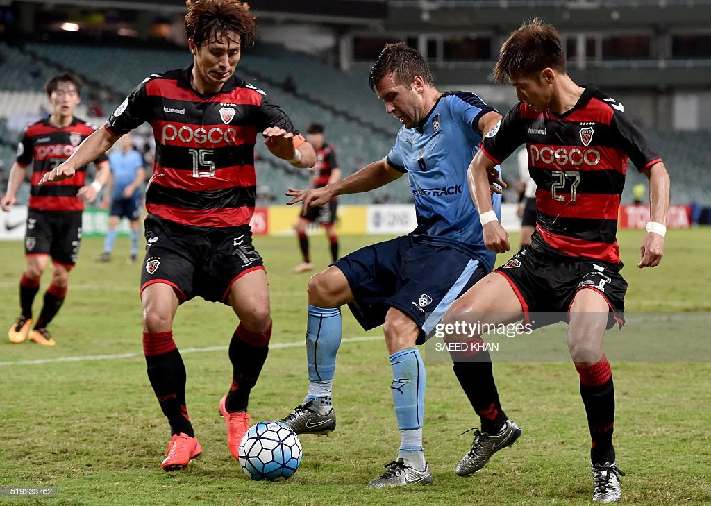 Milos Dimitrijevic (C) of Australia's Sydney FC fights for the ball against Park Sun Ju (R) and Lee Jae Won of South Korea's Pohang Steelers in the Asian Champions League football match in Sydney on April 5, 2016. / AFP / SAEED