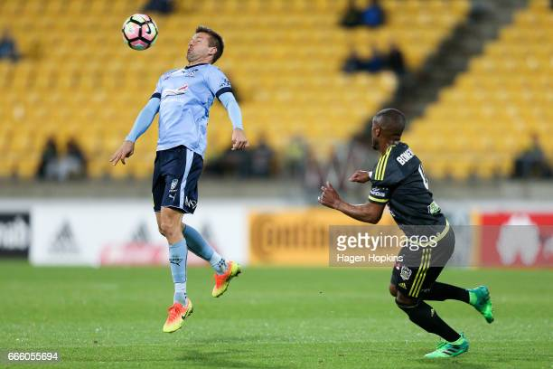 Milos Dimitrijevic of Sydney FC controils the ball under pressure from Roly Bonevacia of the Phoenix during the round 26 ALeague match between the...