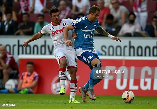 Milos Jojic of Koeln and Pierre Michel Lasogga of Hamburg battle for the ball during the Bundesliga match between 1 FC Koeln and Hamburger SV at...