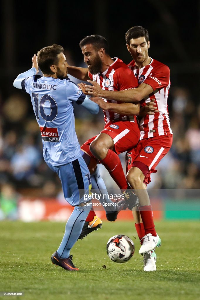Milos Ninkovic of Sydney FC collides with Emmanuel Muscat of City FC and Iacopo La Rocca of City FC during the FFA Cup Quarter Final match between Sydney FC and Melbourne City at Leichhardt Oval on September 13, 2017 in Sydney, Australia.