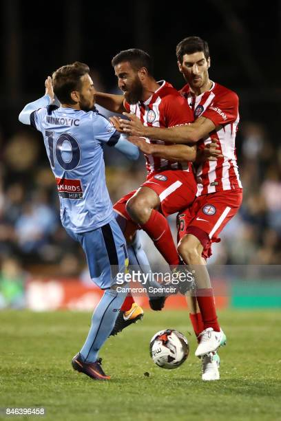 Milos Ninkovic of Sydney FC collides with Emmanuel Muscat of City FC and Iacopo La Rocca of City FC during the FFA Cup Quarter Final match between...