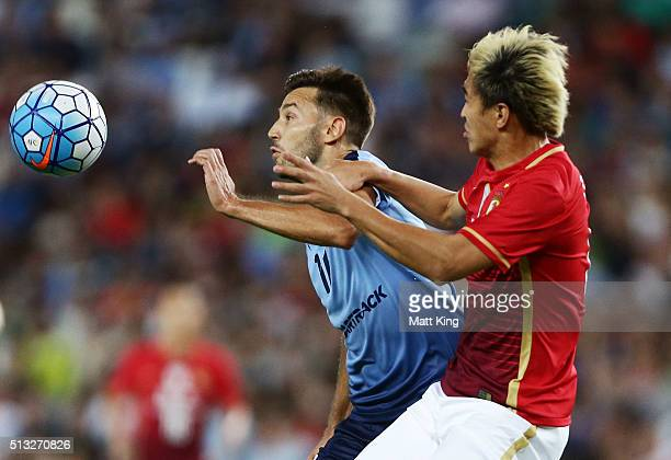 Milos Ninkovic of Sydney FC is challenged by Feng Xiaoting of Guangzhou Evergrande during the AFC Champions League match between Sydney FC and...