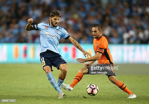 Milos Ninkovic of Sydney FC is challenged by Jack Hingert of the Roar during the round 13 ALeague match between Sydney FC and Brisbane Roar at...