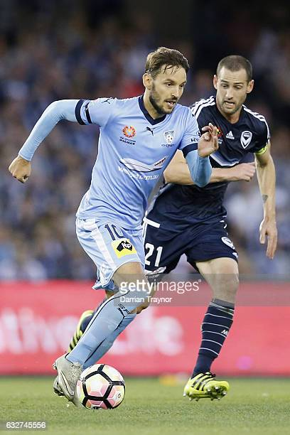 Milos Ninkovic of Sydney FC runs with the ball as Carl Valeri of Melbourne Victory gives chase during the round 17 ALeague match between the...