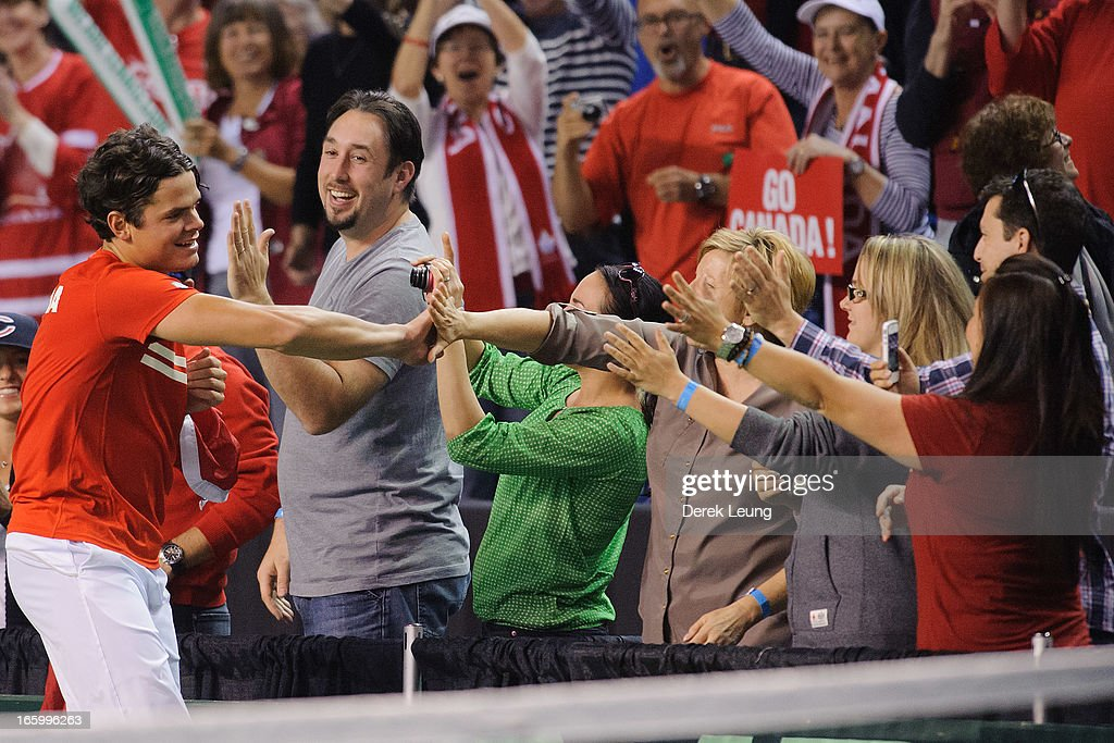 <a gi-track='captionPersonalityLinkClicked' href=/galleries/search?phrase=Milos+Raonic&family=editorial&specificpeople=5421226 ng-click='$event.stopPropagation()'>Milos Raonic</a> of Canada high-fives fans after defeating Andreas Seppi of Italy during his singles match on day three of the 2013 Davis Cup quarterfinals on April 7, 2013 at Doug Mitchell Thunderbird Sports Centre in Vancouver, British Columbia, Canada.