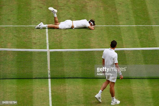 Milos Raonic of Canada looks on as Roger Federer reacts following a Scott Lipsky of The United States during the Men's Singles Semi Final match...