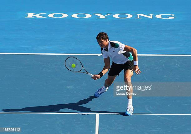 Milos Raonic of Canada plays a forehand during his match against Mardy Fish of the United States during day one of the AAMI Classic at Kooyong on...