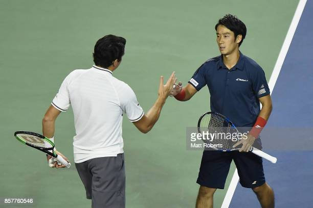 Milos Raonic of Canada shakes and with Yuichi Sugita of Japan after retiring injured during day four of the Rakuten Open at Ariake Coliseum on...