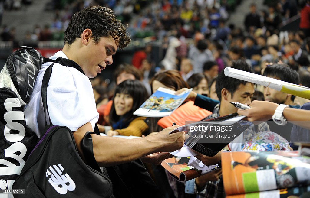 Milos Raonic of Canada (L) signs autographs for fans after his victory over Ivan Dodig of Croatia after their men's singles semi-final match of the Japan Open tennis tournament in Tokyo on October 5, 2013.