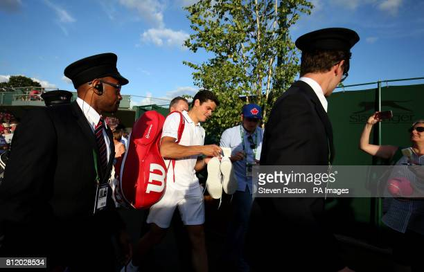 Milos Raonic signs autographs for fans after beating Alexander Zverev on day seven of the Wimbledon Championships at The All England Lawn Tennis and...