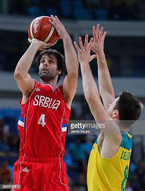 Milos Teodosic of Serbia attempts a shot over Matthew Dellavedova of Australia during the first half of the Men's Semifinal match on Day 14 of the...