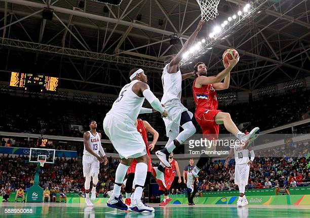 Milos Teodosic of Serbia goes to the basket against Draymond Green and Carmelo Anthony of United States in the Men's Preliminary Round Group A match...