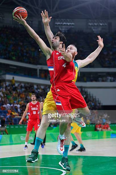 Milos Teodosic of Serbia lays up a shot past Aron Baynes of Australia during the Men's Semifinal match on Day 14 of the Rio 2016 Olympic Games at...