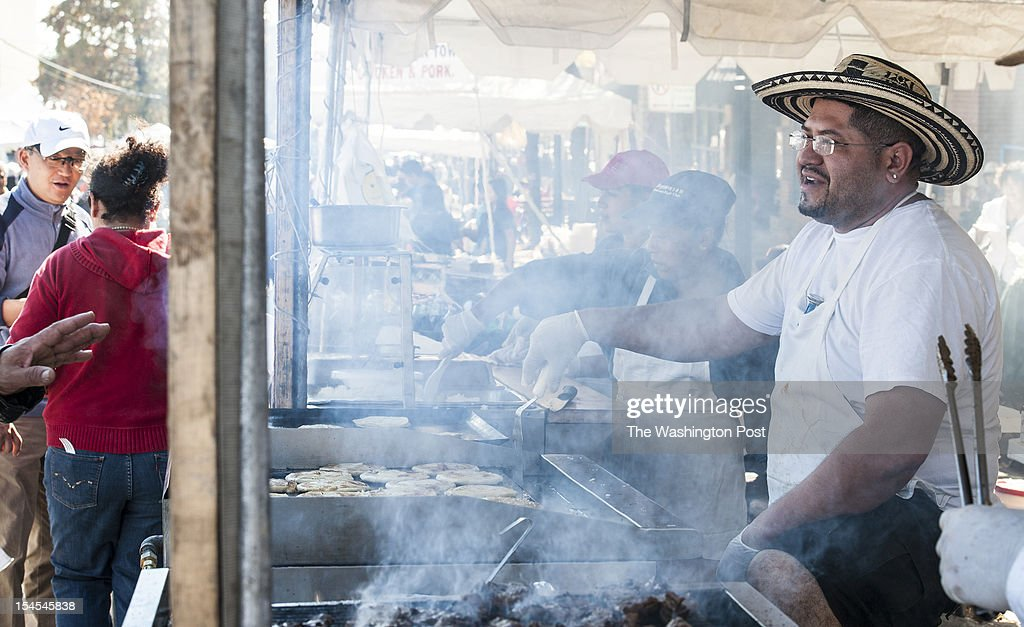 Milton Contreras who owns El Boqueron II with his father flips pupusas through a haze of smoke as he talks with customers at the World of Montgomery...