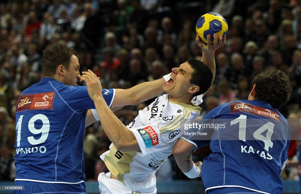 Milutin Dragicevic (C) of Kiel is challenged by Adam Twardo (L) and Bostjan Kavas (R) of Plock during the EHF Champions League second leg match between THW Kiel and Orlen Wisla Plock at Sparkassen Arena on March 18, 2012 in Kiel, Germany.