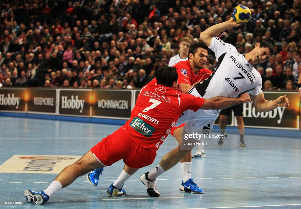 Milutin Dragicevic (R) of Kiel is challenged by Andrei Klimovets (L) and Nenad Vuckovic during the Toyota Handball Bundesliga match between THW Kiel and MT Melsungen at the Sparkassen Arena on February 23, 2011 in Kiel, Germany.