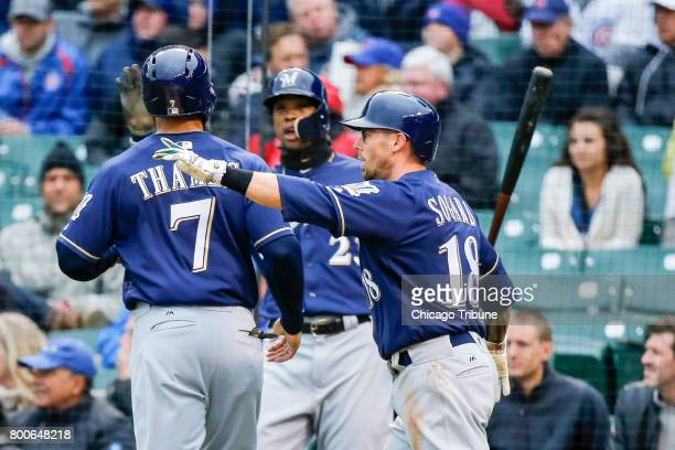 Milwaukee Brewers first baseman Eric Thames and shortstop Eric Sogard score on a single by catcher Jett Bandy against the Chicago Cubs on May 19 at...