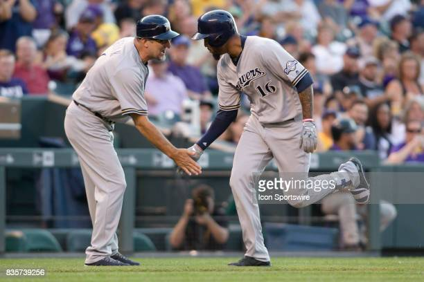Milwaukee Brewers outfielder Domingo Santana celebrates with third base coach Ed Sedar after hitting a home run during the Colorado Rockies game vs...