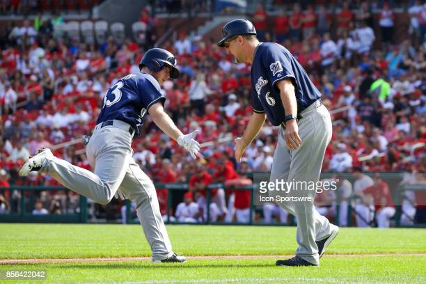 Milwaukee Brewers right fielder Brett Phillips gives Milwaukee Brewers third base coach Ed Sedar a low five after hitting a home run in the first...
