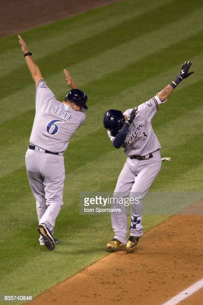 Milwaukee Brewers shortstop Orlando Arcia and third base coach Ed Sedar celebrate after a home run during the Colorado Rockies game vs the Milwaukee...