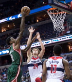Milwaukee Bucks center Larry Sanders scores over Washington Wizards small forward Jan Vesely and power forward Kevin Seraphin during the first half...