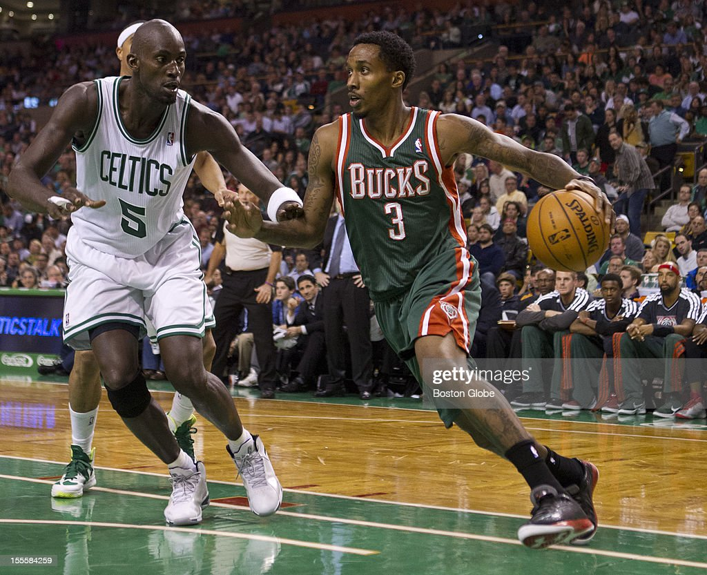 Milwaukee Bucks player Brandon Jennings drives to the basket with defensive pressure from Boston Celtics player Kevin Garnett during second quarter action at TD Garden on Friday, Nov. 2, 2012.