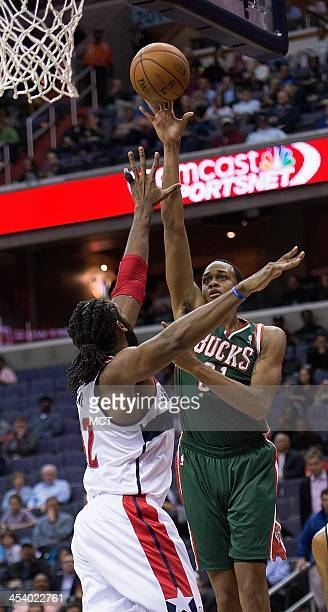 Milwaukee Bucks power forward John Henson shoots over Washington Wizards power forward Nene Hilario during the first half of their game played at the...