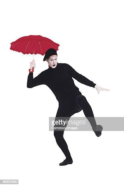 Mime dancing with umbrella