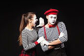 Woman mime shouting in man mime ear on isolated black background