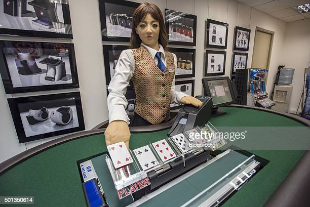Min a prototype humanlike electronic croupier deals a card during a demonstration at the headquarters of Paradise Entertainment Ltd in Macau China on...