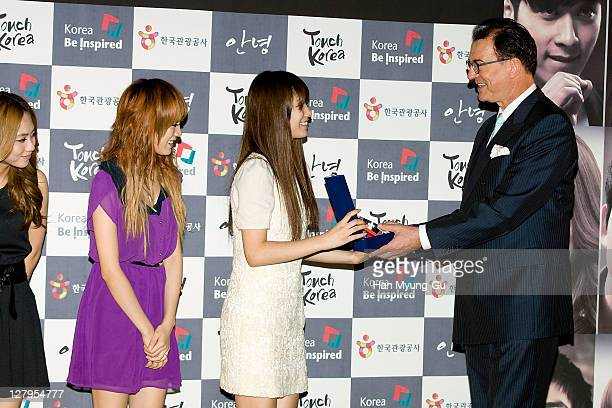 Min Fei Suzy and Jia of Miss A receive an appreciation plaque by Lee Charm CEO of the Korea Tourism Organization as they attend the press briefing...