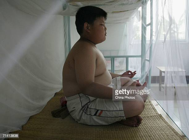 Min Hao a tenyearold Chinese boy sits on a bed during a weightlosing summer camp organized by the Aimin Slimming Centre July 10 2006 in Wuhan of...