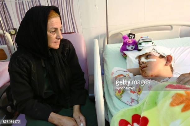 Mina Veysi sits beside her 9yearold son Parsa Veysi at a hospital in Kermanshah western Iran on Nov 16 2017 The boy was buried alive in debris when...