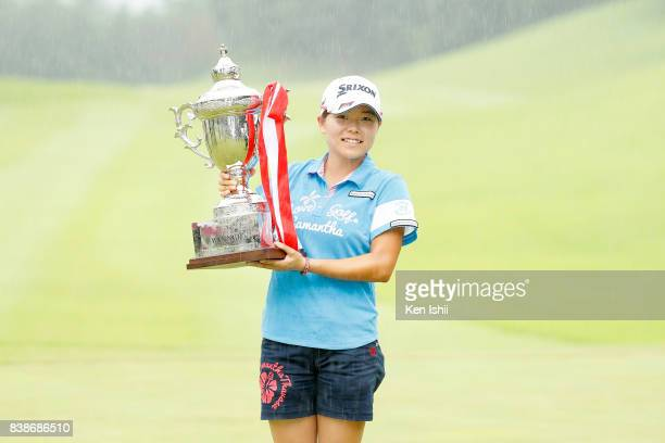 Minami Katsu of Japan poses for photos on the 18th green after winning the final round of the Gogin Duo Card Ladies at the Daisen Heigen Golf Club on...